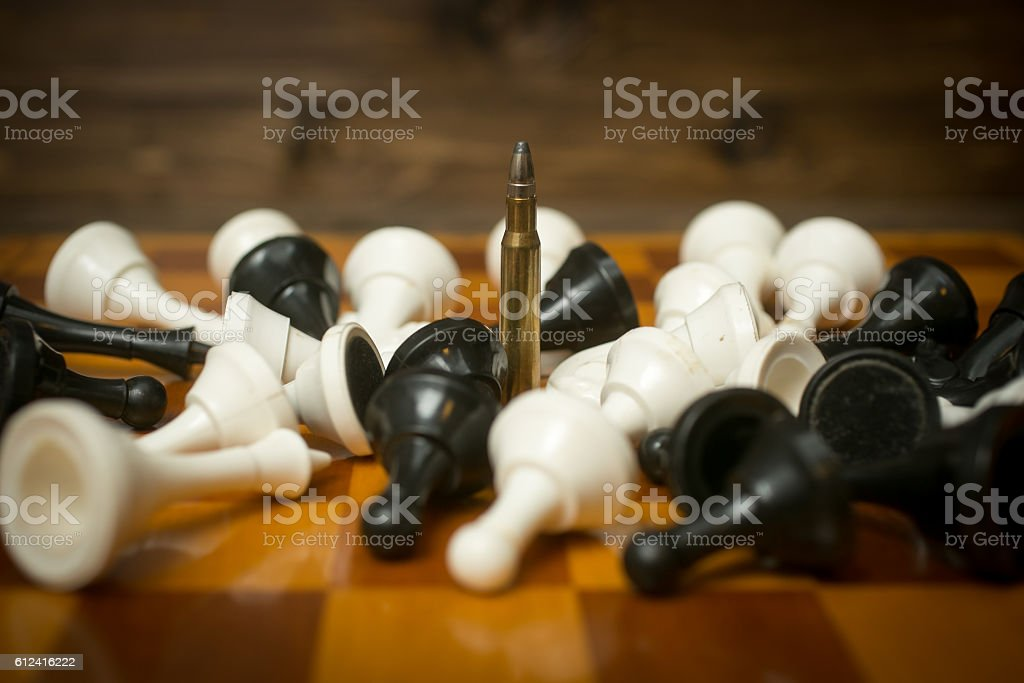 Riffle bullet on chessboard among lying chess pieces stock photo