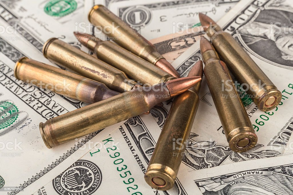 Rifle Bullets on Banknotes stock photo