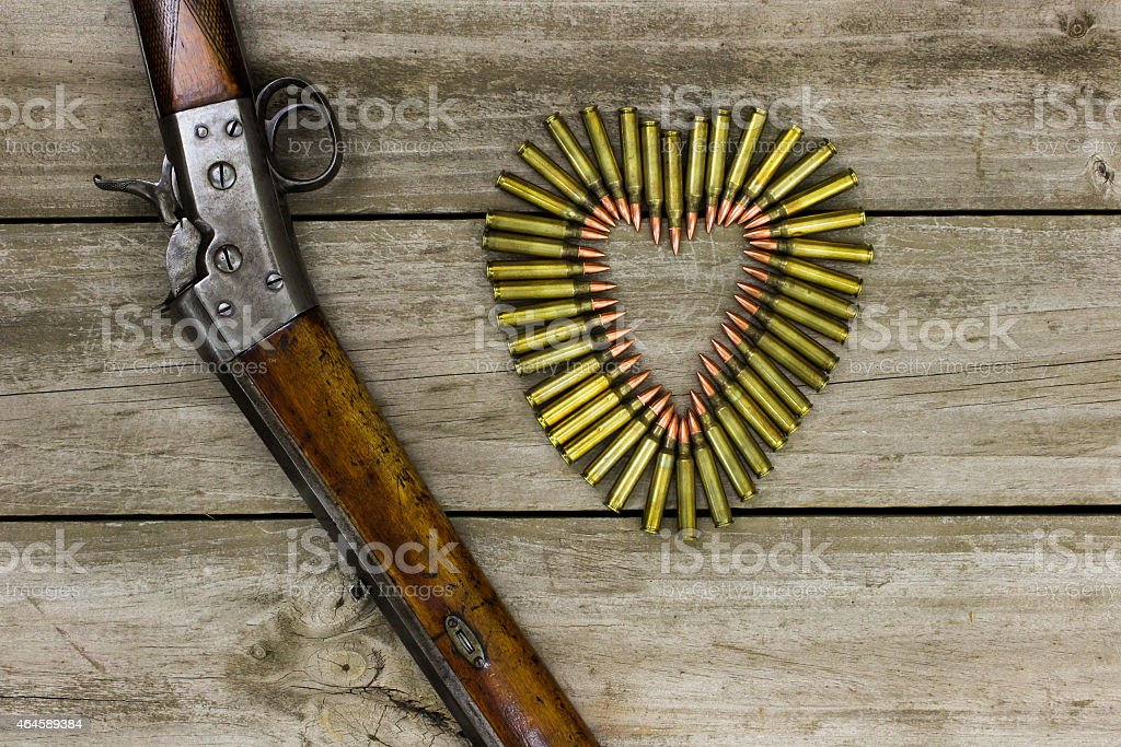 Rifle by bullets in shape of heart stock photo