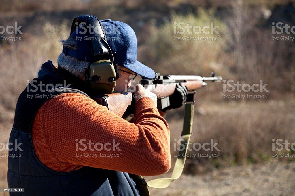 Rifle shooter aiming high powered rifle outdoors stock photo
