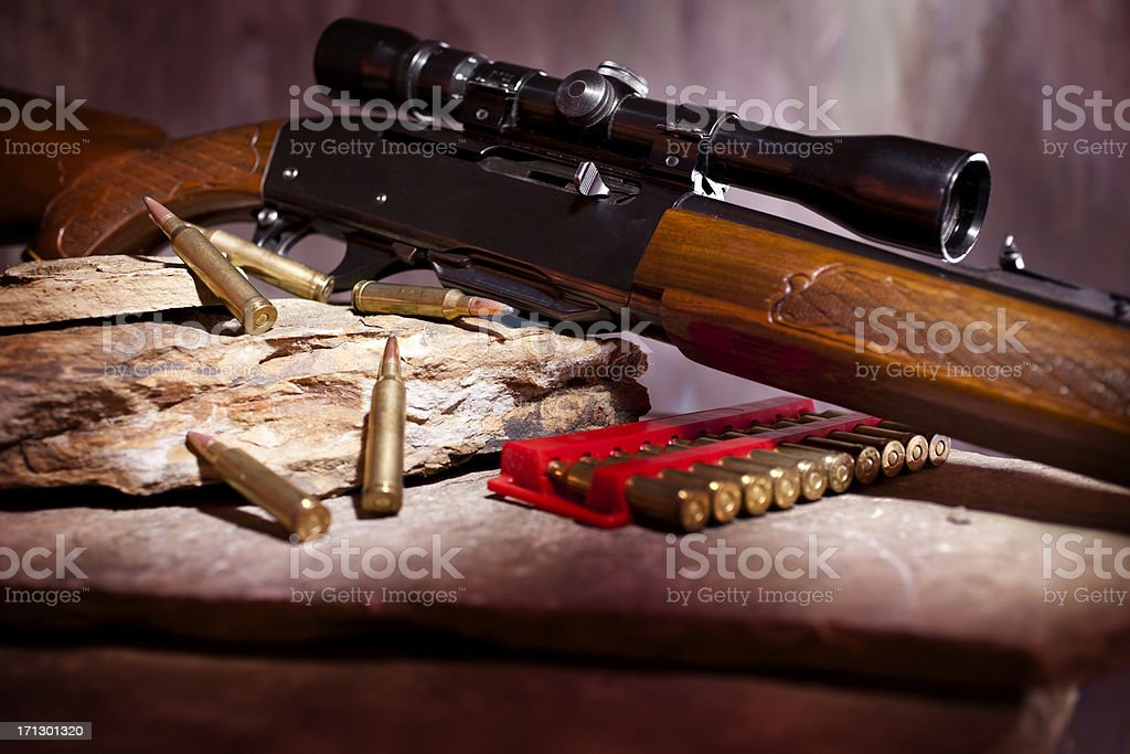 Rifle with sight and ammunition on rock shelf stock photo
