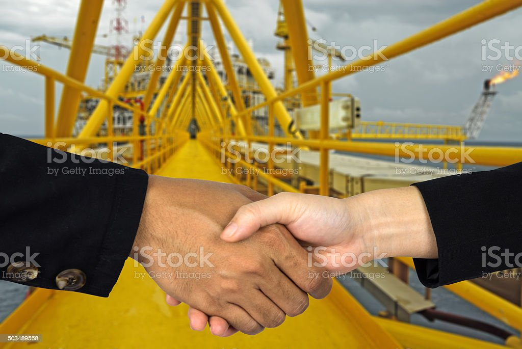 rig background with man and woman shakehands stock photo