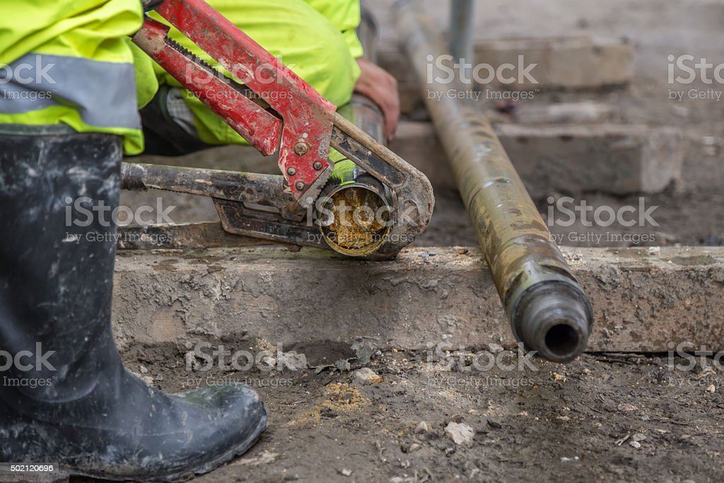 Rig workers at site take out drill core sample stock photo