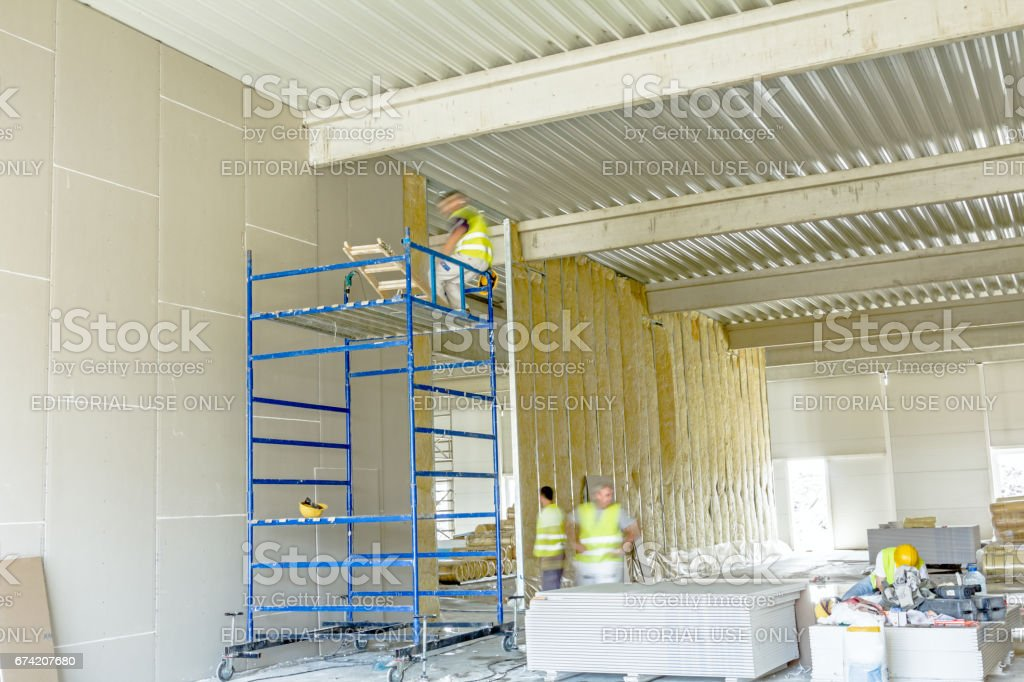 Riggers are working on thermal partition dry wall with mineral wool stock photo