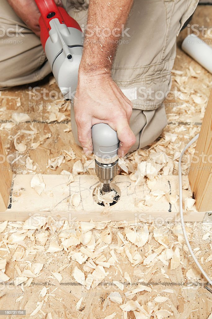 Right Angle Drill Cutting Hole for Plumbing stock photo