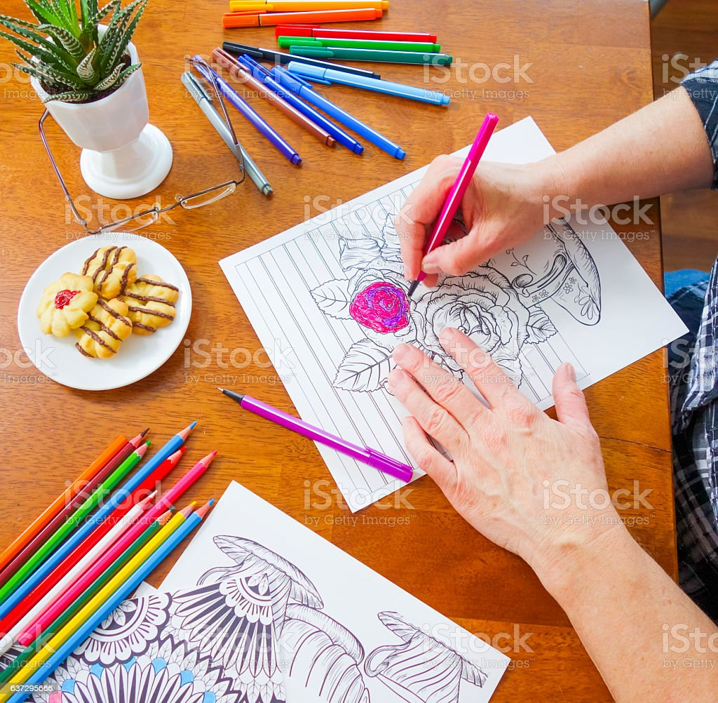 Right Handed Woman Coloring Flowers with Pink Marker stock photo