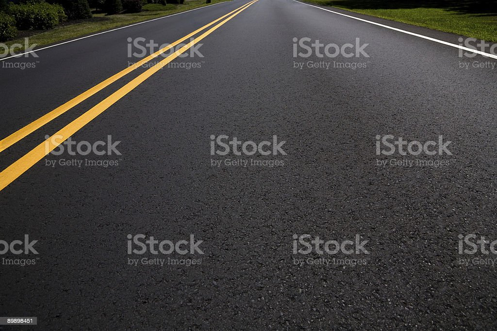 Right Lane of a Freshly Paved Asphalt Road Diminishing Perspective stock photo