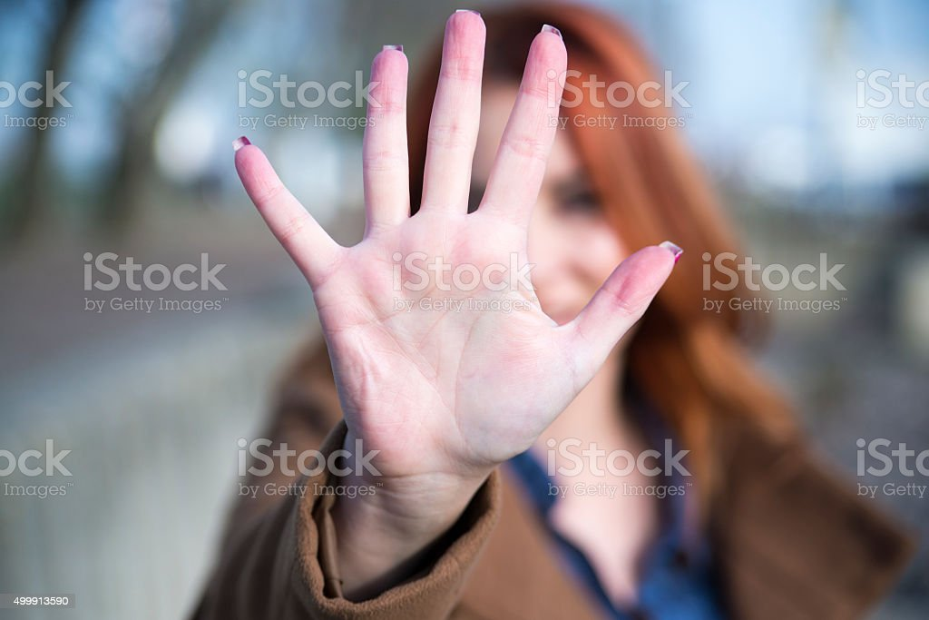 STOP right there woman with hand up stock photo