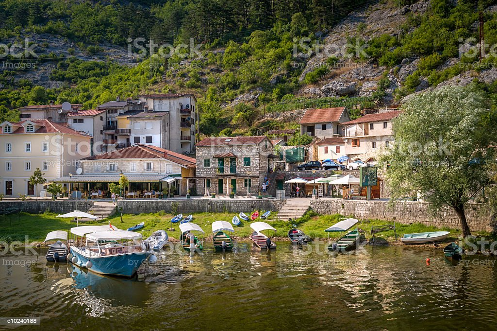 Rijeka Crnojevica old town embankment and river excursions boats moored stock photo