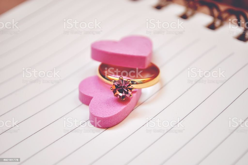 Ring and pink heart on notebook for background stock photo