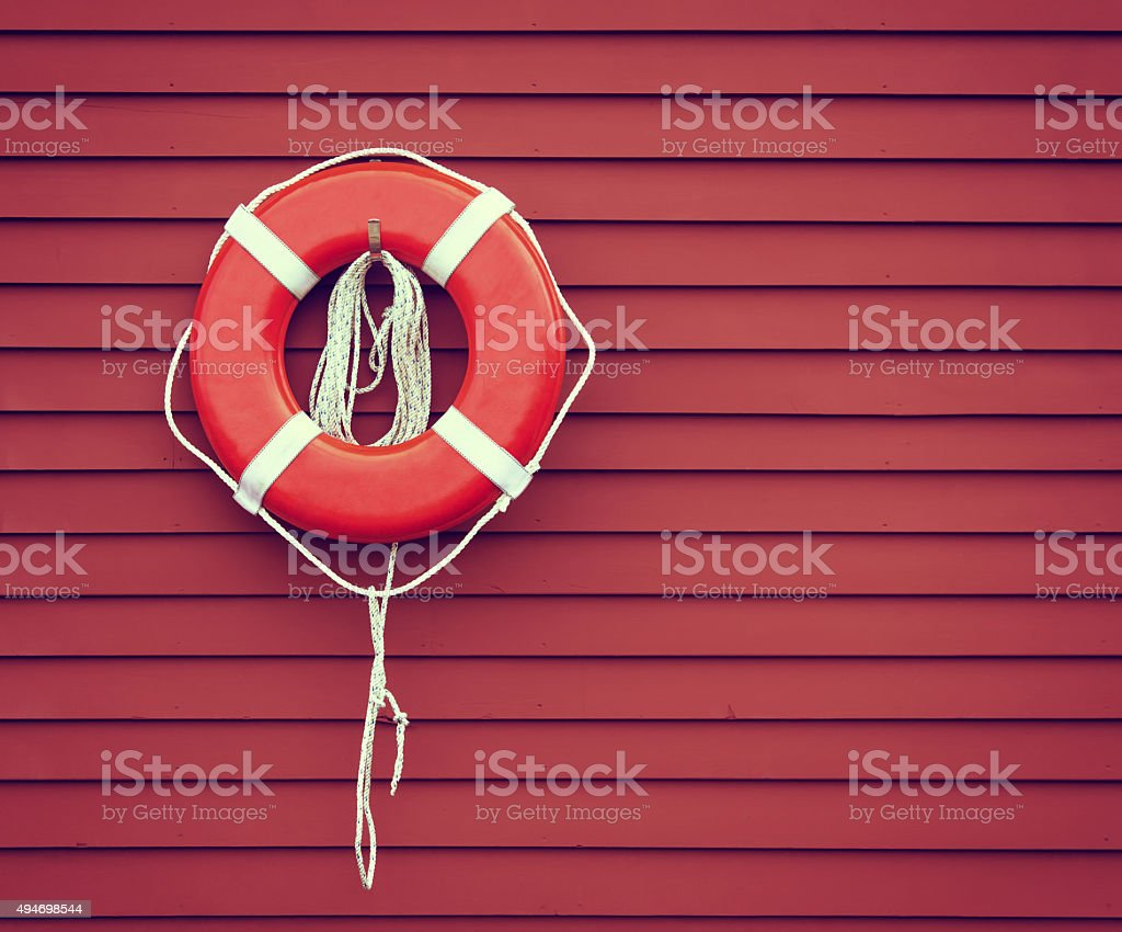 Ring buoy on red wooden wall stock photo