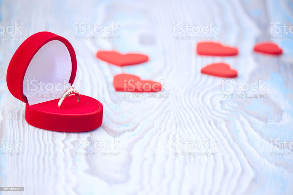 Ring for marriage proposal and red hearts on wooden table. stock photo