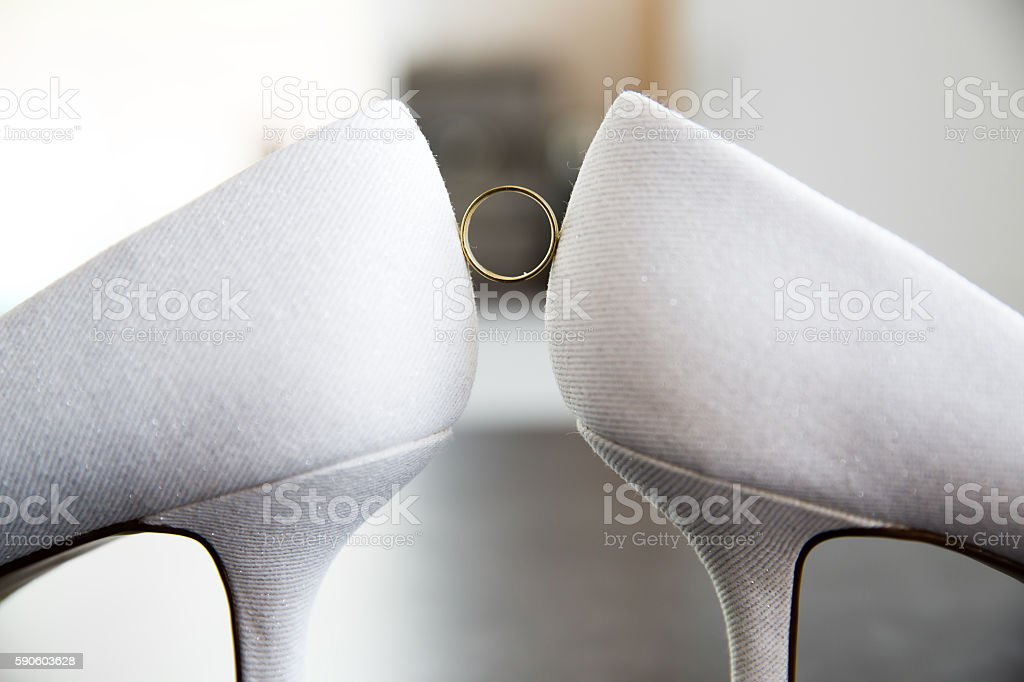 Ring hold by bridal high heels stock photo