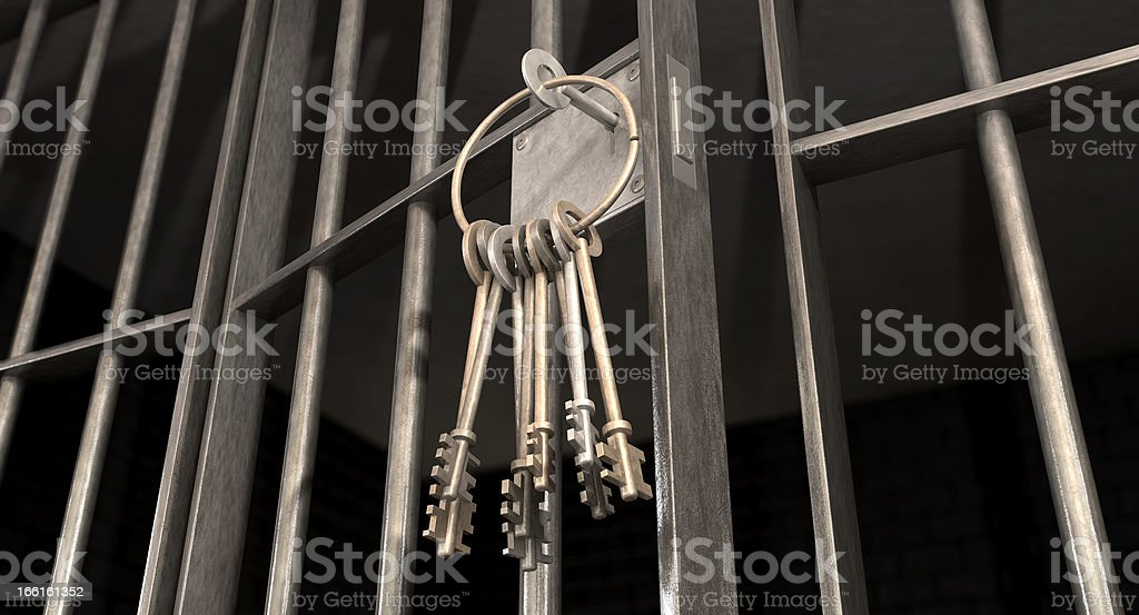 Ring of keys hanging from a slightly ajar jail cell door stock photo