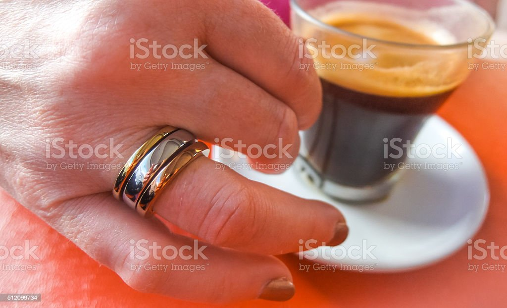 Ring on her finger, espresso in a cup. stock photo