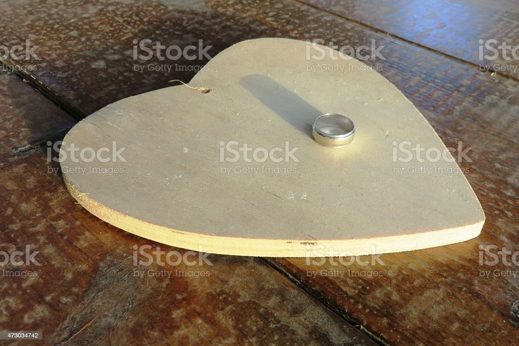 Ring resting on a wooden heart stock photo