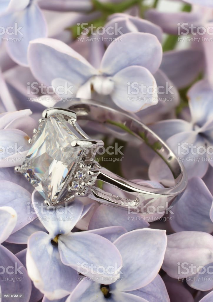 Ring with big diamond on violet flower stock photo