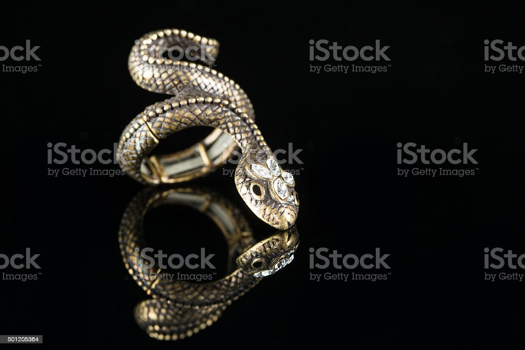 ring with stones in the form of snake on black stock photo