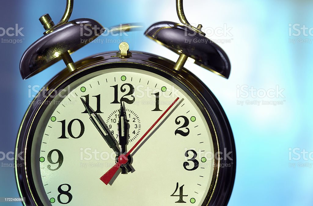 Ringing alarm clock displaying five to twelve stock photo