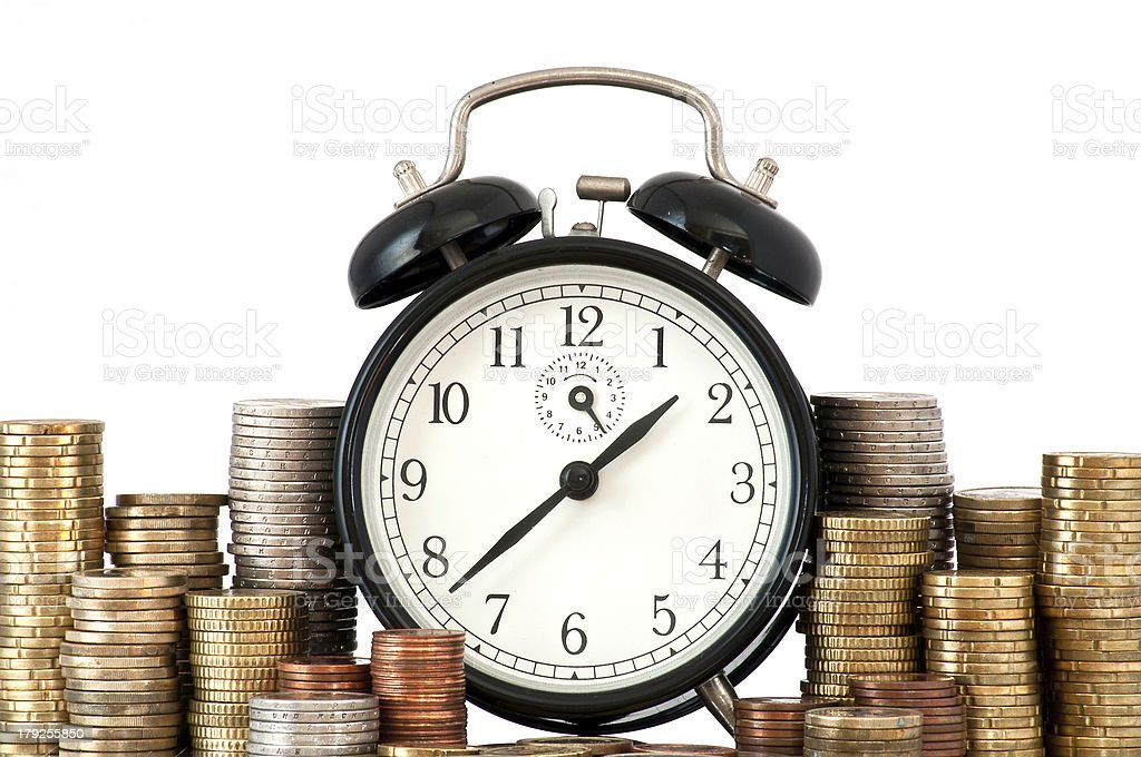 A ringing clock sitting between piles of coins stock photo
