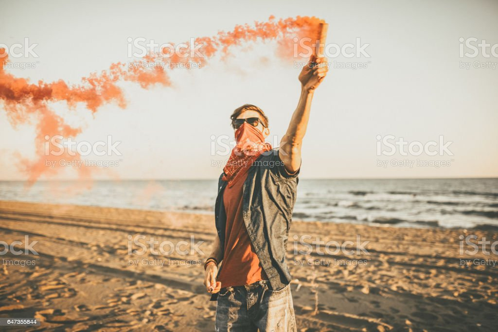 Riot Hipster Man holding red smoke on the beach stock photo