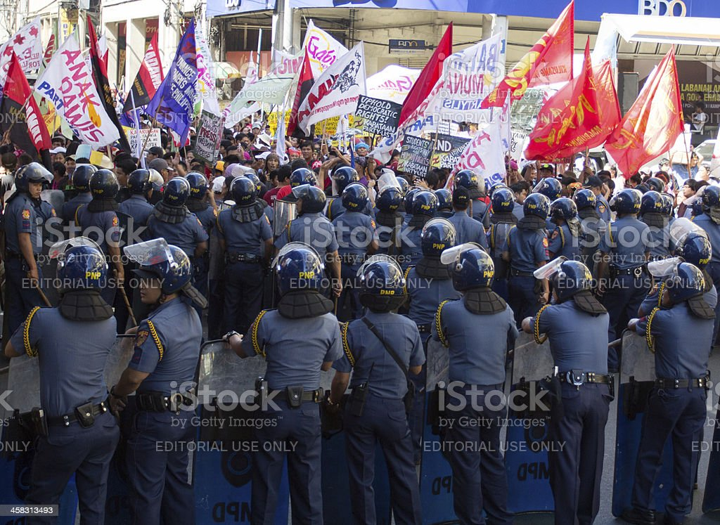 Riot police stand guard against demonstrators royalty-free stock photo