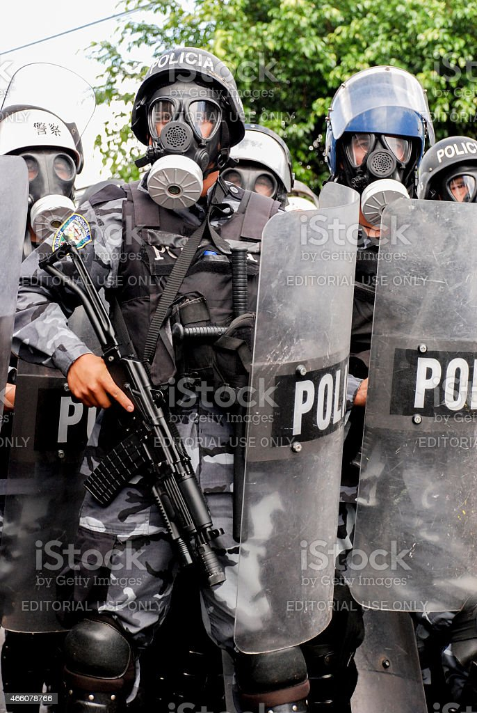 Riot police with shields and guns stock photo