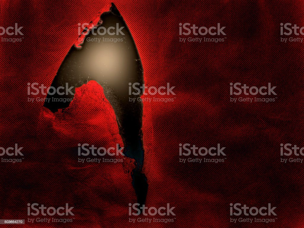 Rip, tear in fabric reveals light. Looks science fiction universe. stock photo