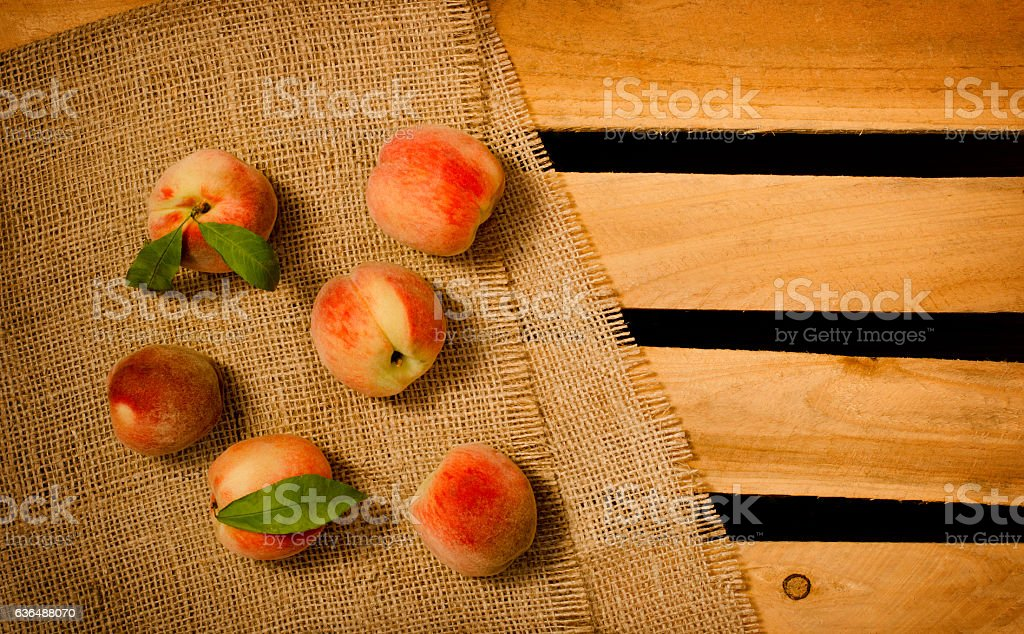 Ripe appetizing peach on sacking, wooden box, top view stock photo
