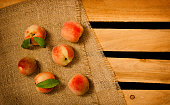 Ripe appetizing peach on sacking, wooden box, top view