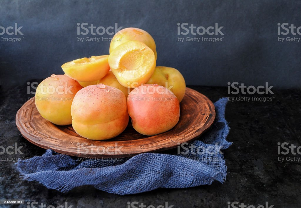 Ripe apricots in a plate on a dark background stock photo