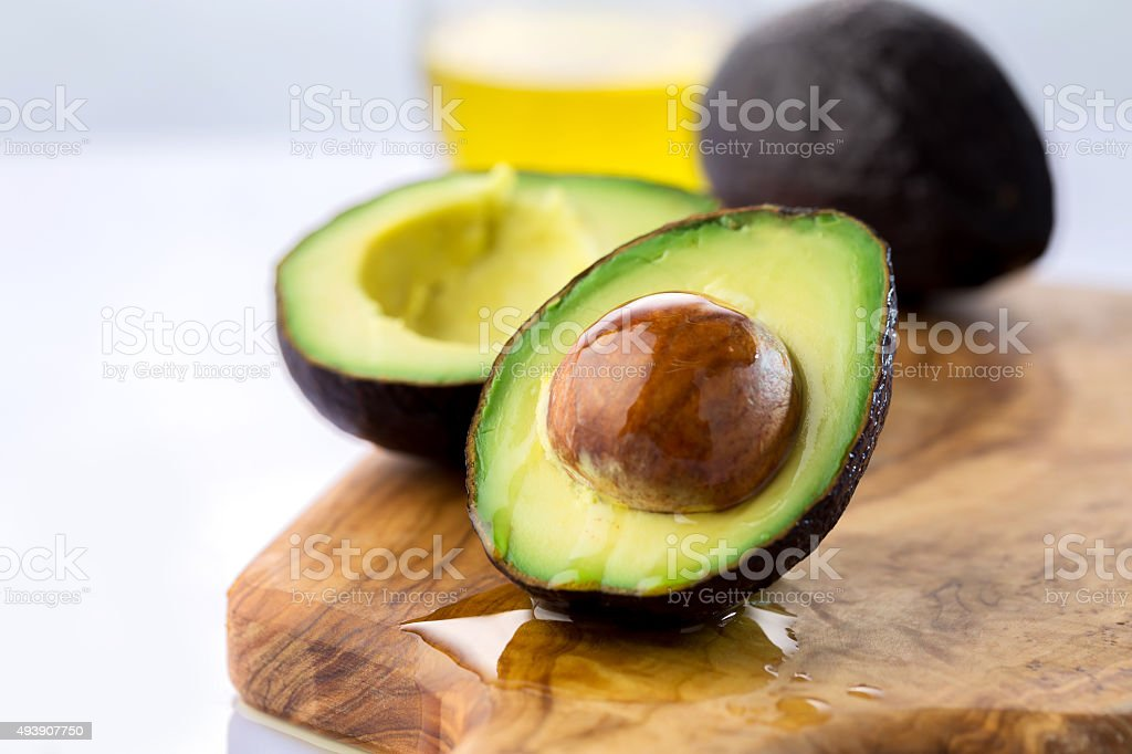ripe avocado cut in half on white background stock photo