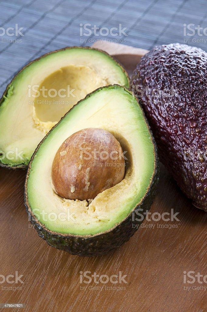 Ripe avocado on wooden plate. Closeup. royalty-free stock photo