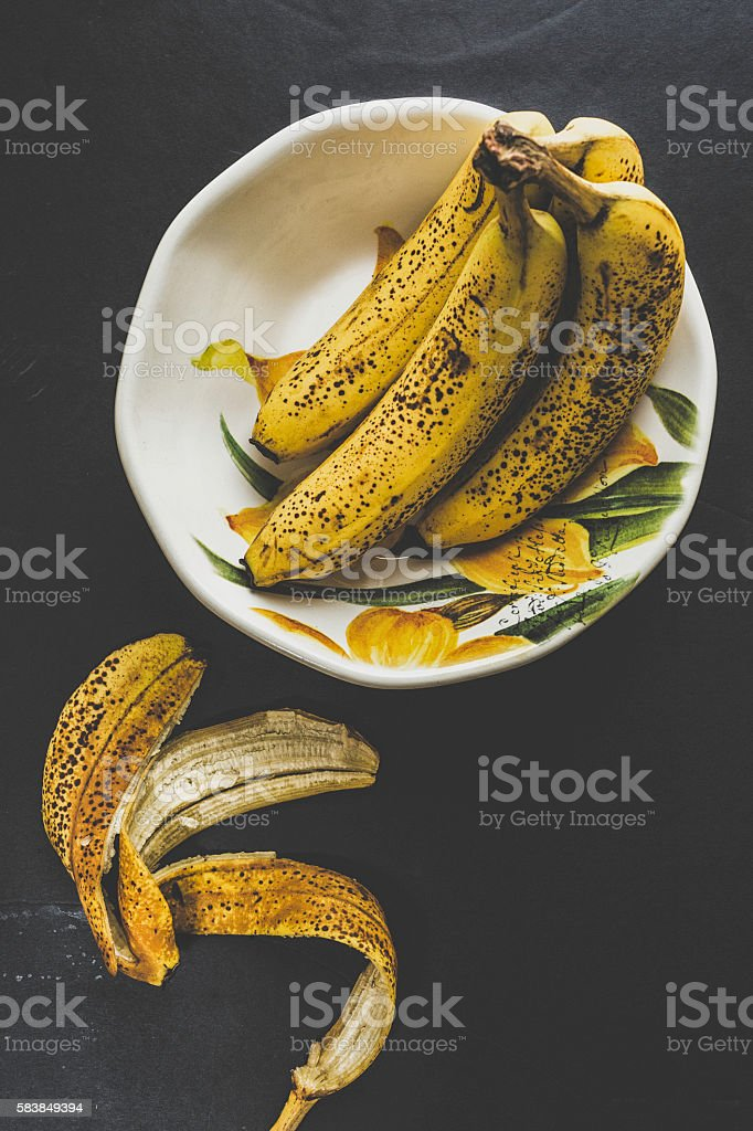 Ripe Bananas Into A Colorful Bowl On Black Background stock photo