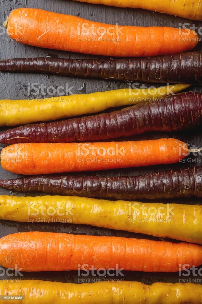 Ripe black, orange and yellow carrots. Dark stone background. Autumn harvest. top view stock photo
