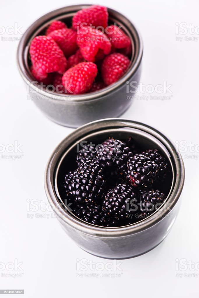 Ripe blackberries and raspberries in saucers stock photo