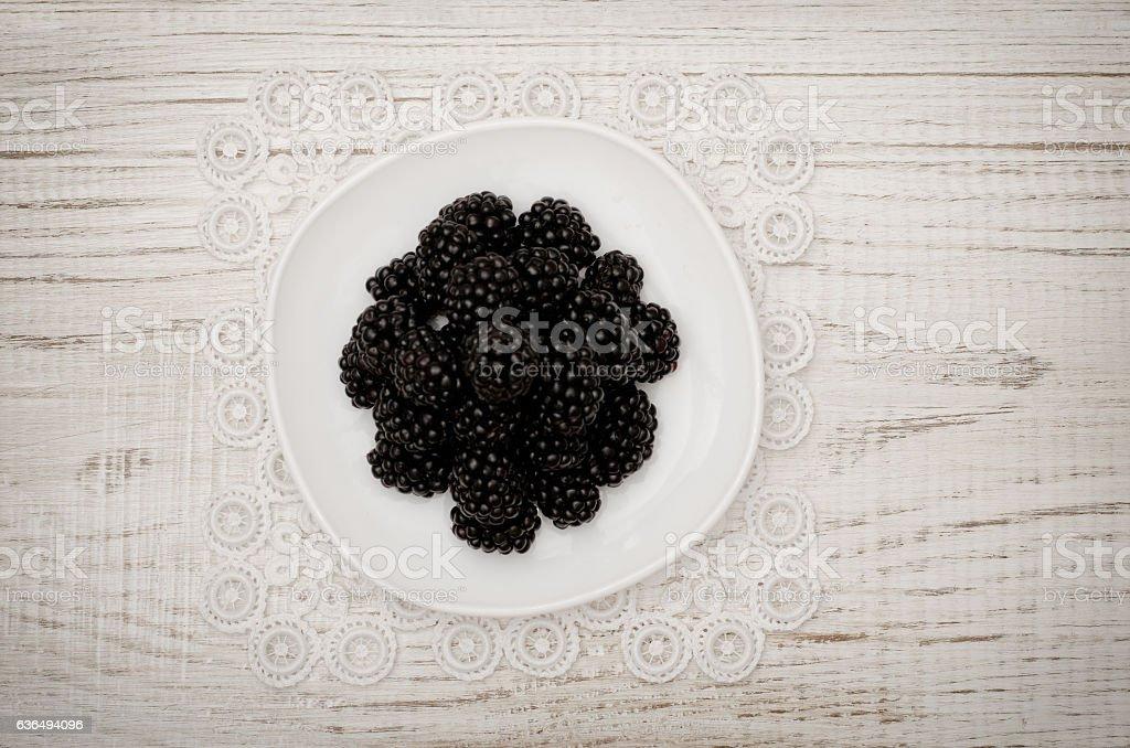 Ripe blackberries on a white saucer. white wooden table stock photo
