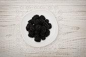 Ripe blackberries on a white saucer. white wooden table