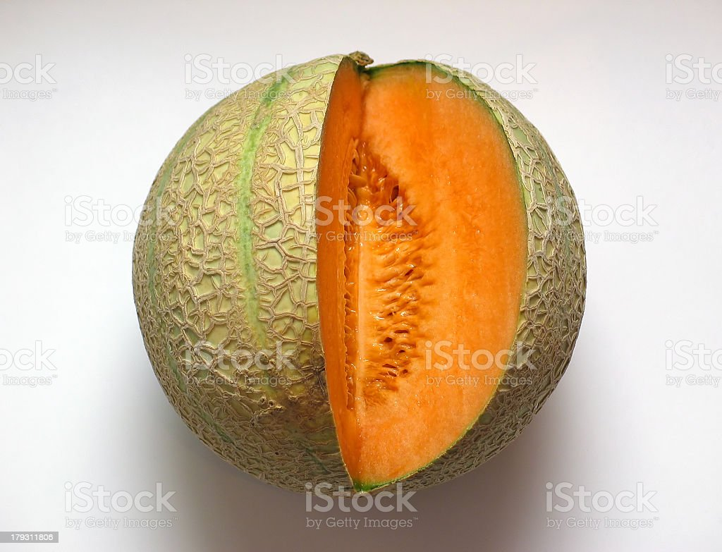 A ripe cantaloupe with a wedge cut out of it stock photo