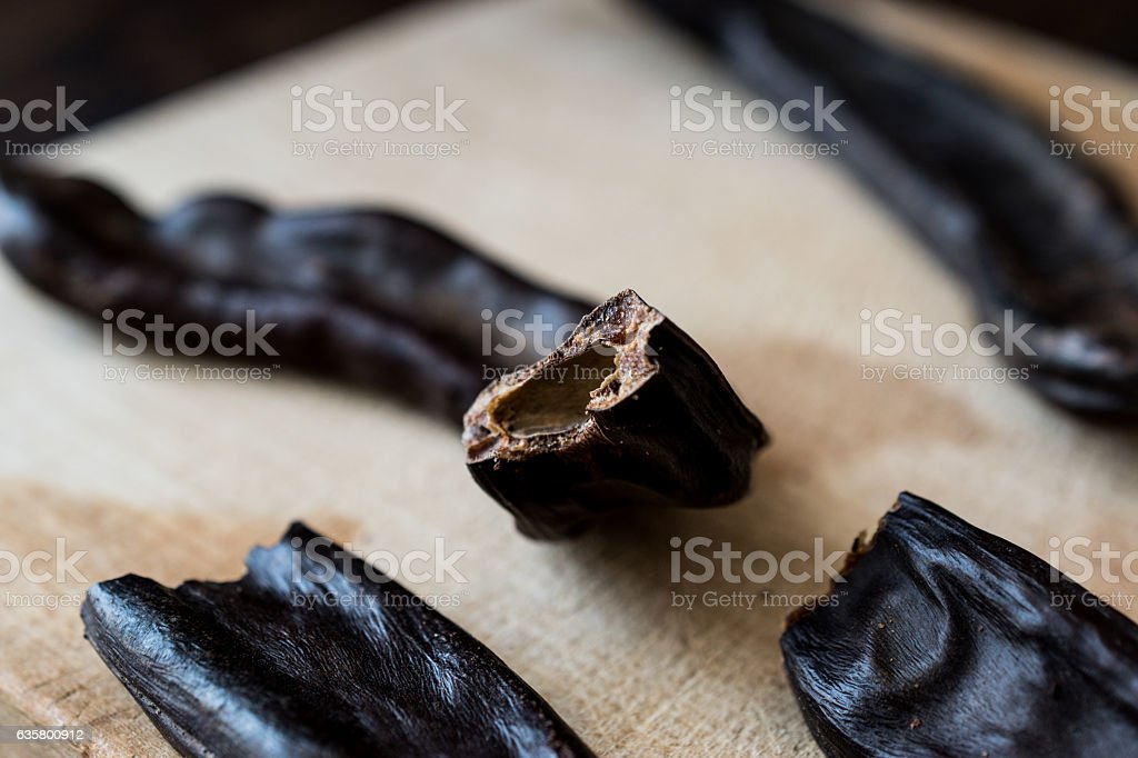 Ripe Carob Pods on wooden surface. stock photo