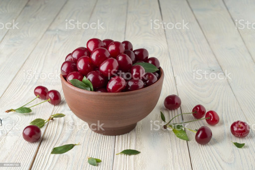 ripe cherries and leaves in a bowl on a textured wooden background stock photo