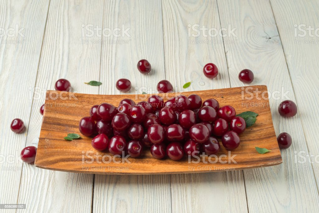 ripe cherries and leaves in a wooden plate on a textured wooden background stock photo