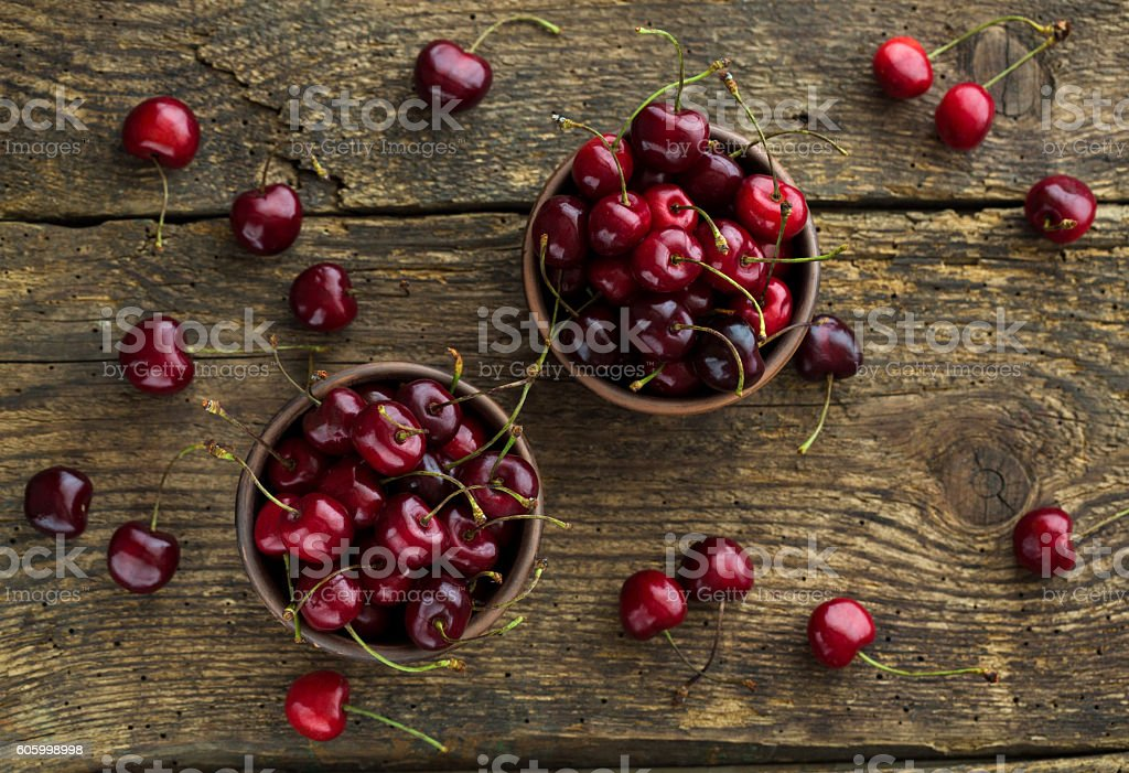 Ripe cherries in a clay bowl on wooden background stock photo
