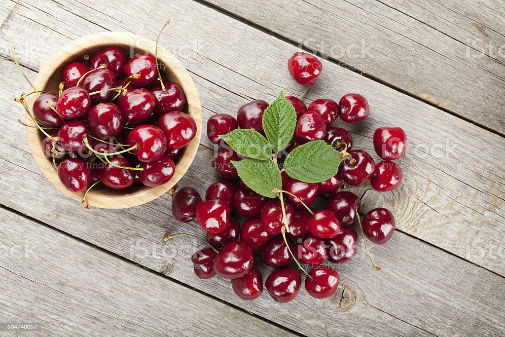 Ripe cherries on wooden table stock photo