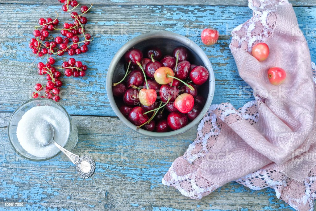 Ripe cherry in a bowl on an old wooden surface stock photo