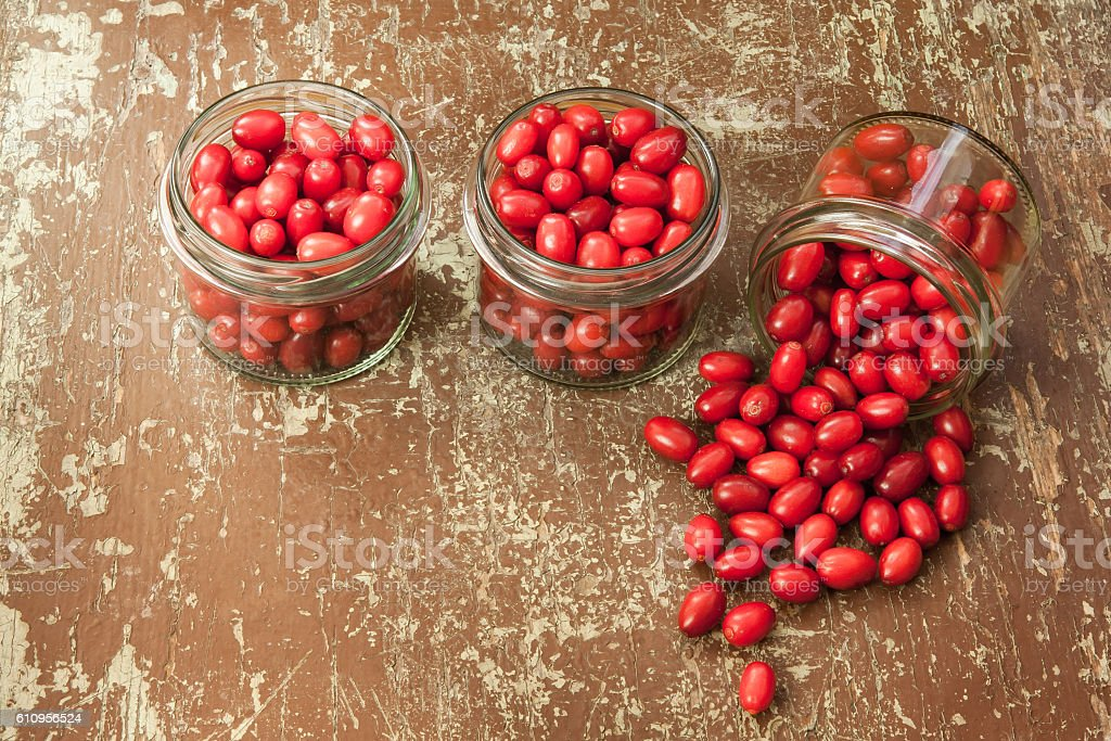 Ripe cornelian cherry in glass jars stock photo
