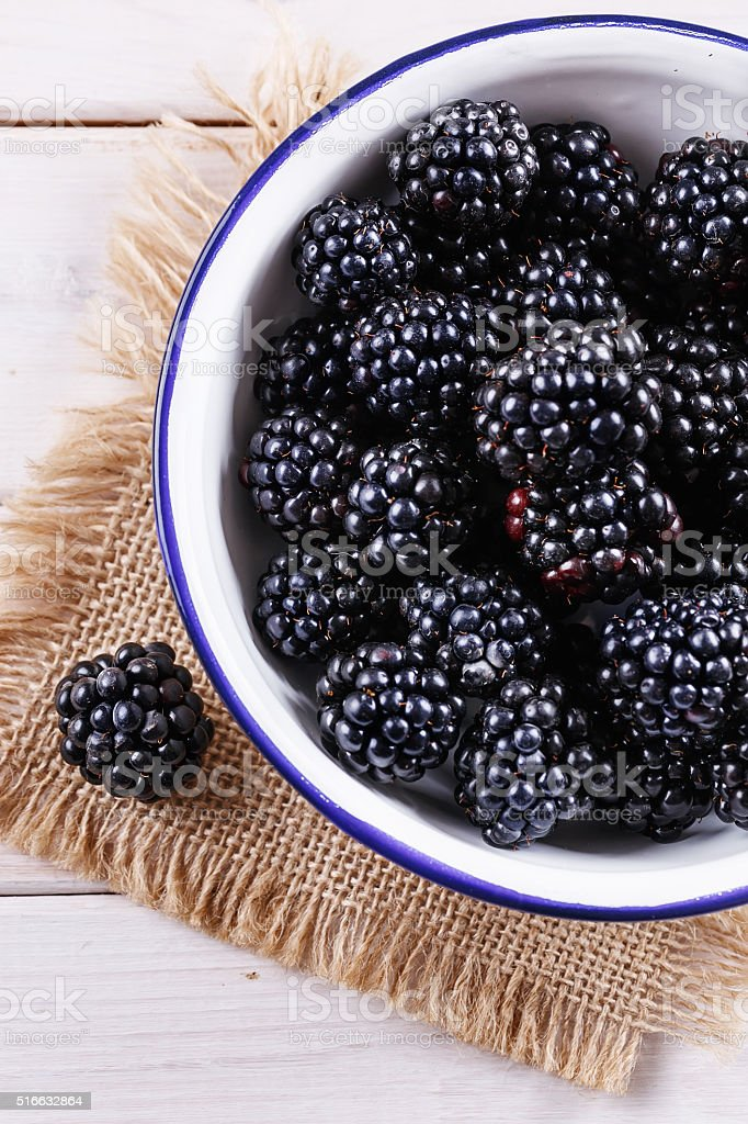 Ripe fresh blackberries in a plate on wooden rustic background stock photo