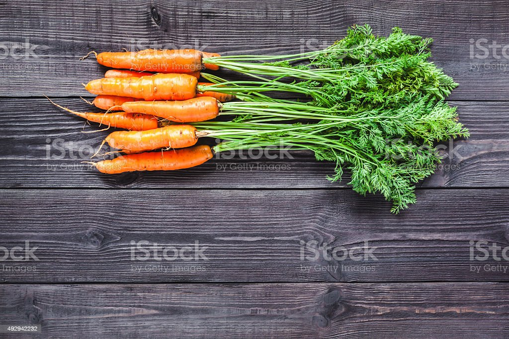 Ripe fresh carrots on a wooden background. stock photo