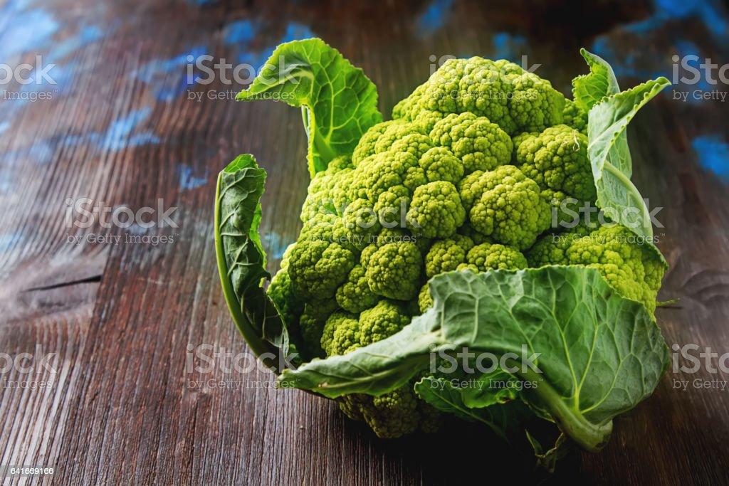 Ripe green cauliflower with leaves. Dark wood background. stock photo