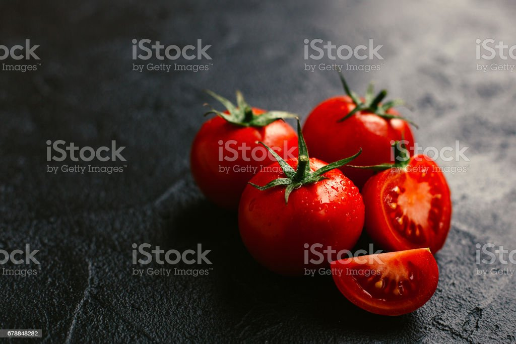 Ripe juicy tomatoes on a dark background stock photo